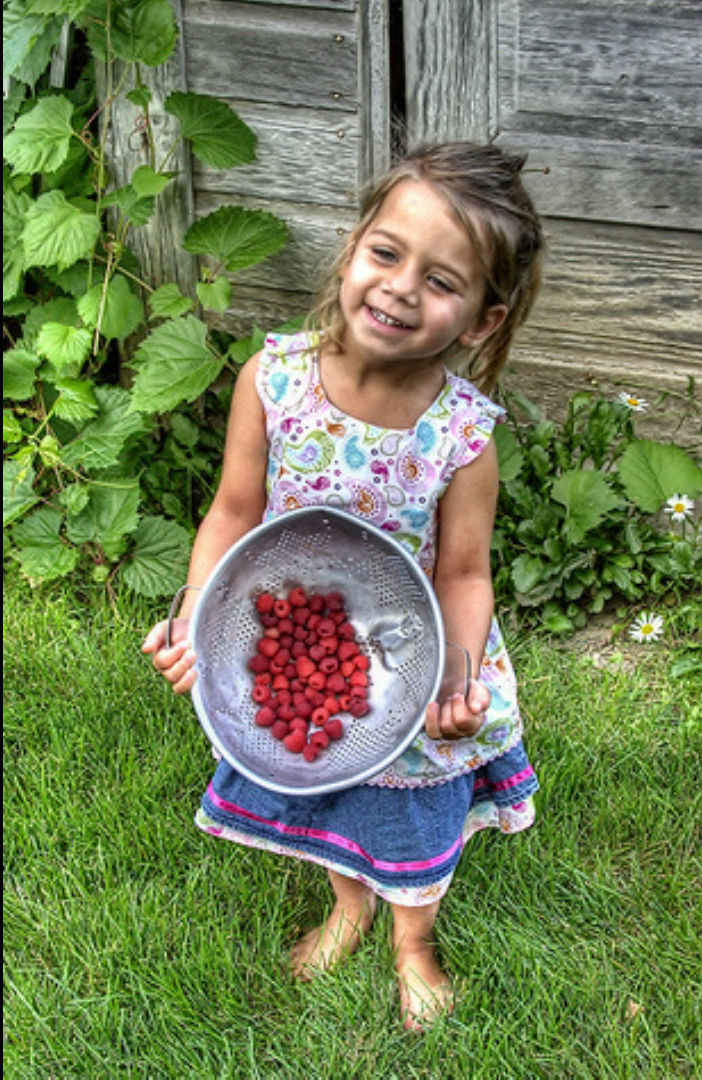 Girl holding a bowl of Raspberries